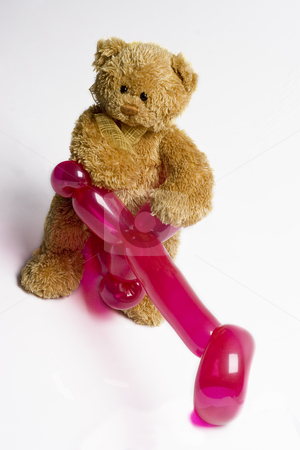 Bad to the fur stock photo, Teddy bear sitting on a pink balloon bike by Yann Poirier