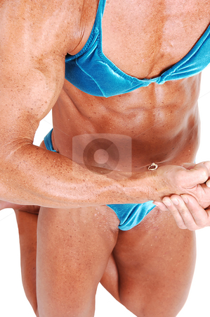 Bodybuilding woman. stock photo, A muscular bodybuilding woman kneeling in the studio shooing her strong  arms and legs, the biceps and and her flat tummy, over white background. by Horst Petzold
