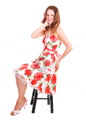 Woman sitting on chair. stock photo, Lovely young woman in high heels and beautiful colored dress sitting on a  chair in the studio with long brown hair. On white background. by Horst Petzold