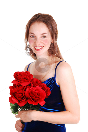 Pretty girl with red roses. stock photo, Pretty young woman standing in the studio in an royal blue velvet dress, holding a bunch of red rose in her hand. For white background. by Horst Petzold