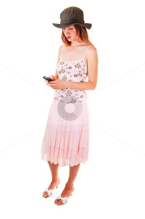 Woman dialing on the phone stock photo, Pretty young woman in a pink skirt and top and high heels, dialing on her cell phone wearing an olive green hat. For white background. by Horst Petzold