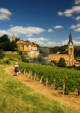 Beaujolais girl stock photo, Image shows a blond country girl walking on a gravel road in a village in the French wine-making region of Beaujolais by Andreas Karelias