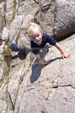 Climbing boy stock photo, Young boy, climbing a big rock on using his hands and feet by Corepics VOF