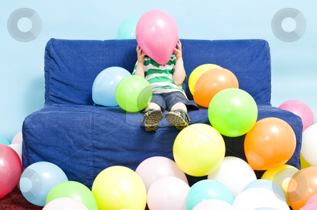 Balloon boy stock photo, Young boy sitting on a couch, hiding behind a baloon he's holding by Corepics VOF
