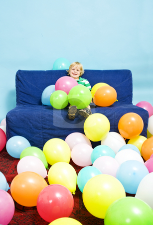 Baloon boy stock photo, Young boy, sitting on a couch, surrounded by baloons by Corepics VOF