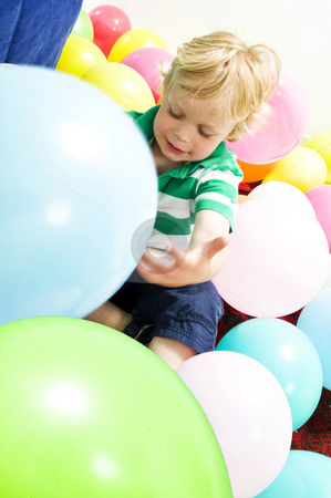 Playing with baloons stock photo, Young boy sitting on the floor, playing with balloons by Corepics VOF