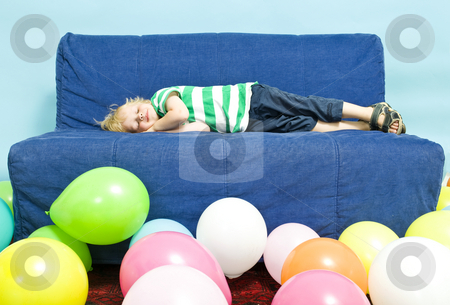 Sleeping boy stock photo, Young child sleeping on a couch, surrounded by baloons by Corepics VOF