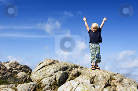 Boy reaching top stock photo, Young boy with his arms raised in victory on top of a rock, conceptual image for conquering challenges, pushing the boundaries, and continuous improvement by Corepics VOF