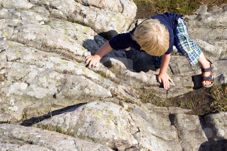 Climbing boy stock photo, Young child, climbing a big rock on using his hands and feet by Corepics VOF