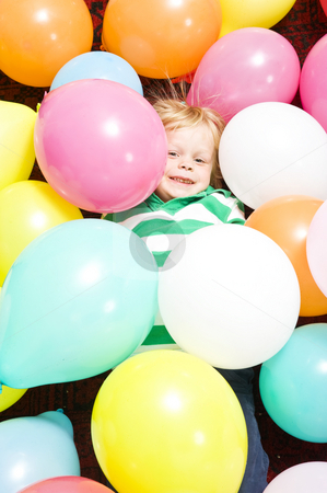 Boy surrounded by baloons stock photo, Young child, happily lying on the floor surrounded by baloons by Corepics VOF