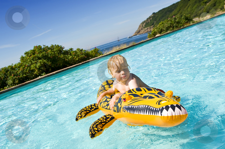Boy in pool stock photo, Young boy playing with an inflatable crocodile in an outdoor pool near the sea by Corepics VOF
