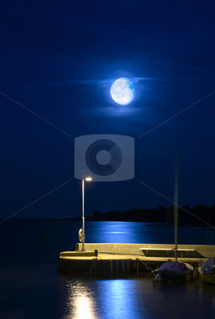 Rising moon stock photo, Rising moon over a tranquil harbor pier by Corepics VOF