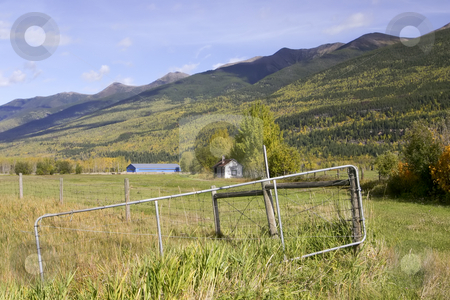 250 Landscape of mountains and fields stock photo, Wire gate hanging in front of hay field by Sharron Schiefelbein