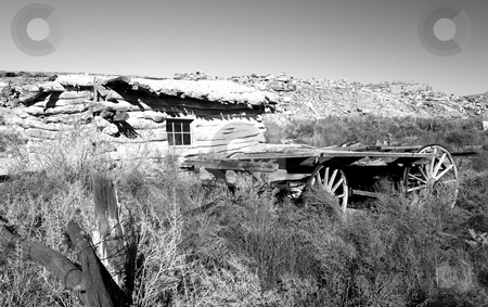 Old cabin and wagon stock photo, Black & white of an old cabin and wagon by Sharron Schiefelbein