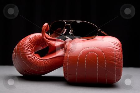 Boxing gloves and sunglasses stock photo, Men's sunglasses place on top of boxing gloves by Yann Poirier