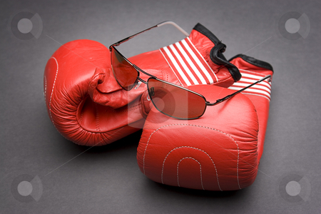 Fight and gambling stock photo, Men's sunglasses place on top of boxing gloves by Yann Poirier