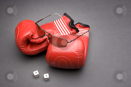 Fight and gambling stock photo, Men's sunglasses place on top of boxing gloves with a pair of dice rolled on snake eyes by Yann Poirier