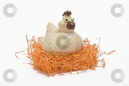 Nesting chicken stock photo, Chocolate chicken nesting in a nest of orange straw by Yann Poirier