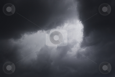 Dark storm stock photo, Light patch of light in the middile of dark storm cloud by Yann Poirier