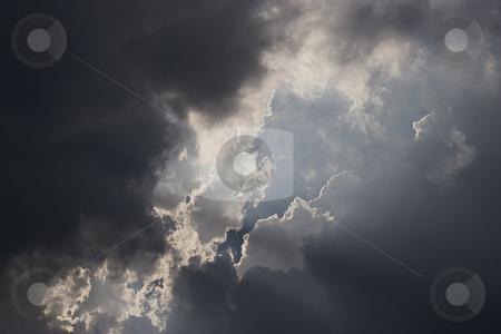 Dark cloud stock photo, Dark cloud with ray of light piercing throught a hole by Yann Poirier