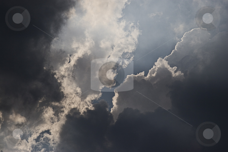 Dark cloud stock photo, Dark cloud with ray of light piercing throught a hole by Yann Poirier