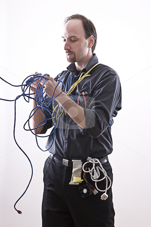 TECHNICIAN EATING CABLE  stock photo, Technician taking a bite out of some blue network cable by Yann Poirier