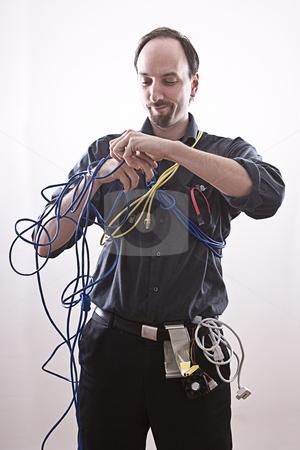 Entangle technician stock photo, Computer technician entangle in network cable by Yann Poirier