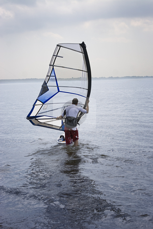Windsurfer stock photo, Windsurfer heading out in the water early in the morning by Yann Poirier