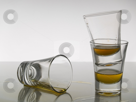 Three shots of whiskey stock photo, Three shots of whiskey on white background over gray floor. by Ignacio Gonzalez Prado