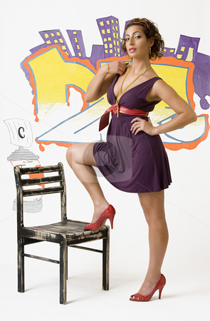 Adjusting dress stock photo, Young women with a foot on a wood chair in front of graffiti adjusting dress by Yann Poirier