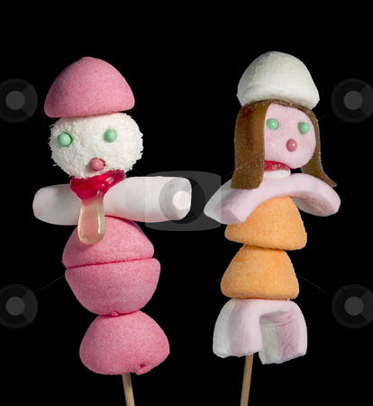 Candy people stock photo, A male and a female figurin made out of candies on a stik over a black background. by Ignacio Gonzalez Prado