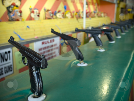 Shoot the clown stock photo, Aiming attraction with several wold war II styled toy guns. by Ignacio Gonzalez Prado