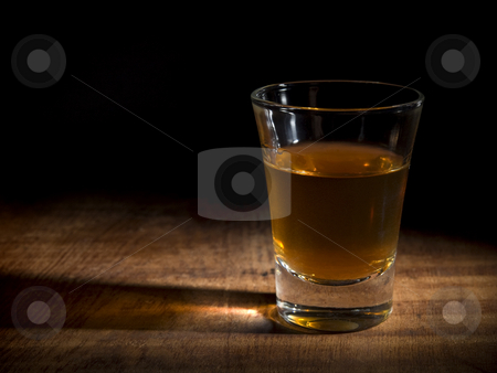 Shot in the dark stock photo, A single shot of an aged liquor over a wooden table. by Ignacio Gonzalez Prado