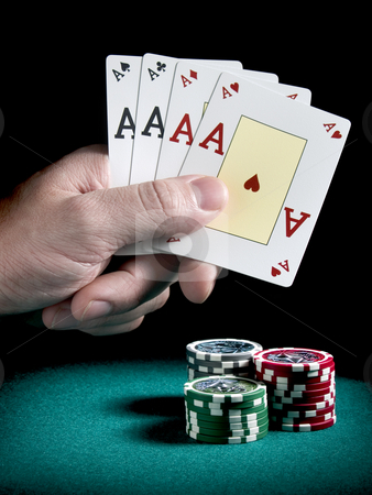 Four aces stock photo, A man's hand holding four aces over three piles of differents colors chips on a green felt. by Ignacio Gonzalez Prado