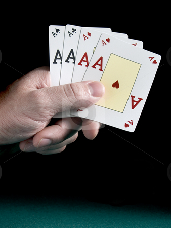 Four aces stock photo, A man's hand holding four aces isolated on black background. by Ignacio Gonzalez Prado