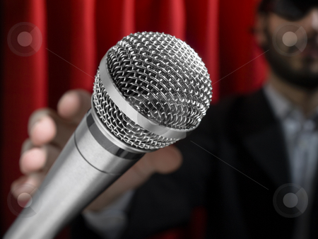 Grab the mic stock photo, A young man on stage about to grab a microphone. by Ignacio Gonzalez Prado