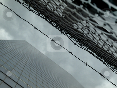 New York building stock photo, High modern skyscraper on a background of a cloudy sky with a fence and a barbwire. by Ignacio Gonzalez Prado
