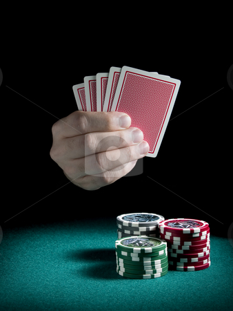 Gambling hand stock photo, A man's hand holding five cards over three piles of differents colors chips on a green felt. by Ignacio Gonzalez Prado