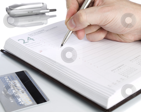 Open notebook stock photo, A notebook open on december twenty fourth, a credit card and a cellphone. by Ignacio Gonzalez Prado
