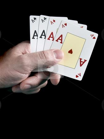 Four aces stock photo, A man's hand holding four aces isolated on black background. by Ignacio Gonzalez Prado