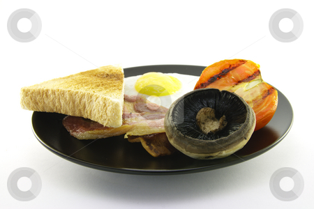 Breakfast and Toast on a Black Plate stock photo, Slices of crispy pork bacon with half a grilled tomato a fried egg, mushroom and a slice of lightly toasted bread on a black round plate with a white background by Keith Wilson