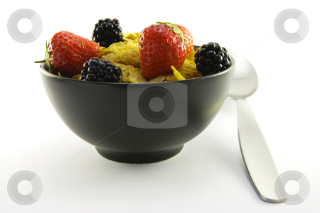 Cornflakes and Fruit in a Black Bowl with a Spoon stock photo, Cornflakes with strawberries and blackberries in a round black bowl with a spoon on a white background by Keith Wilson