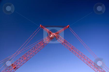 Massive Crane stock photo, Massive red crane creates a cross in the sky. by Charles Buegeler