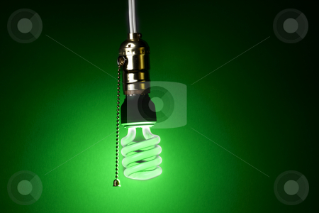 Green compact fluorescent bulb stock photo, Glowing green compact fluorescent bulb hangs from a light socket by James Barber