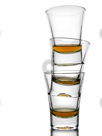 Three shots of whiskey stock photo, A pile of three almost empty shots of whiskey on white background with reflex. by Ignacio Gonzalez Prado