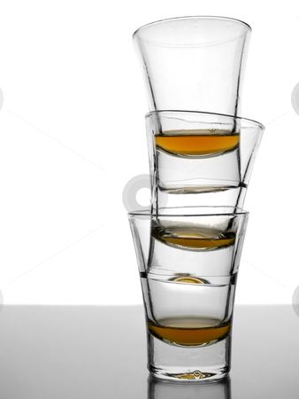 Three shots of whiskey stock photo, A pile of three almost empty shots of whiskey on white background over gray floor. by Ignacio Gonzalez Prado