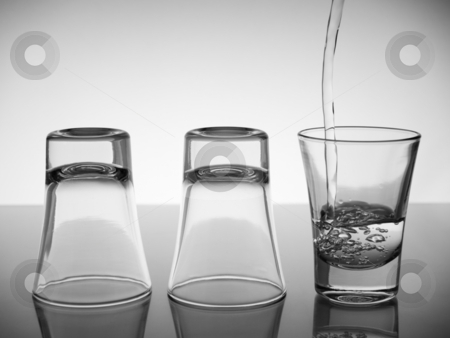 Three shots of vodka stock photo, Three shots, two turned upside down and one being poured with vodka. by Ignacio Gonzalez Prado