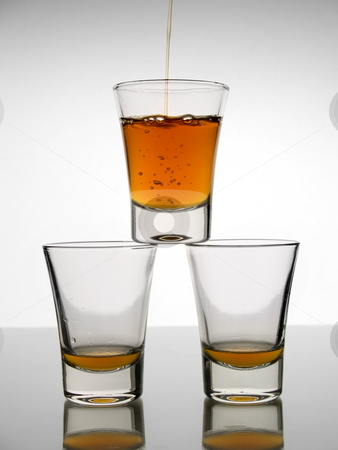 Three shots of whiskey stock photo, A shot being poured with whiskey over other two almost empty shots. by Ignacio Gonzalez Prado