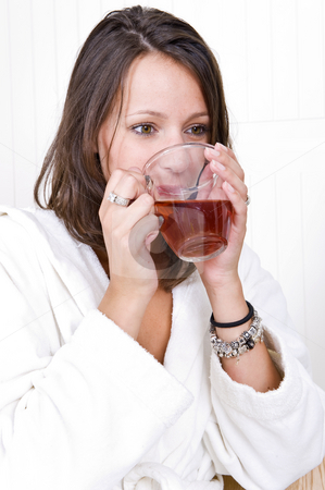 Woman drinking tea stock photo, Young woman, dressed in a bathrobe, drinking a cup of tea by Corepics VOF