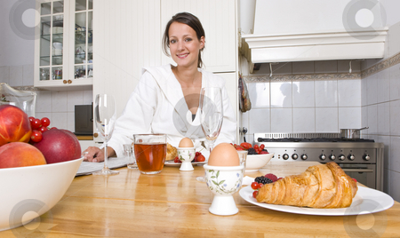 Breakfast stock photo, Young woman enjoying a rich breakfast at a kitchen counter with fruit, croissants, eggs, and the morning paper by Corepics VOF